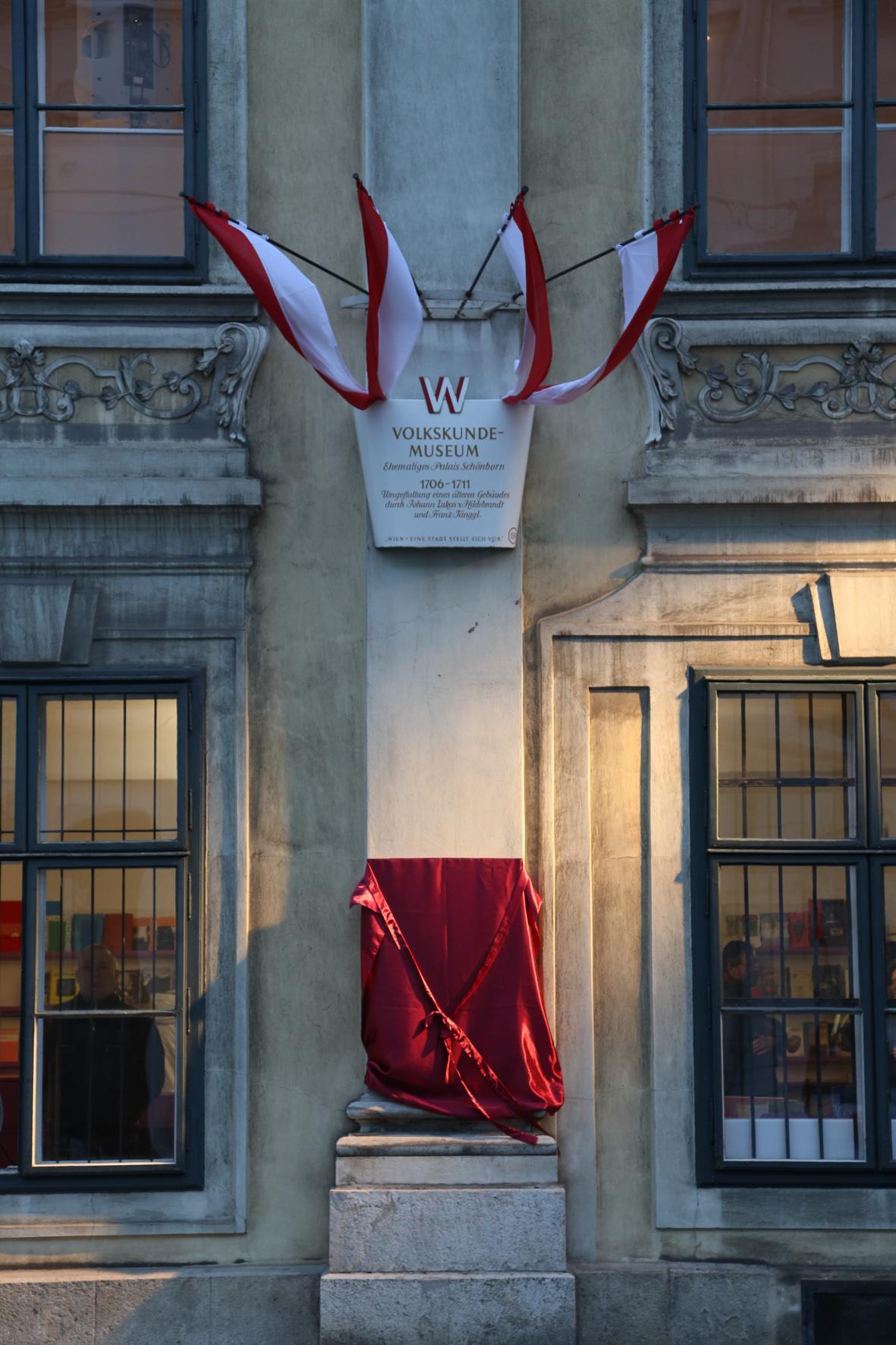 Foto zur feierlichen Enthüllung der Erinnerungstafel, die mit einem roten Tuch und Band verhüllt ist.