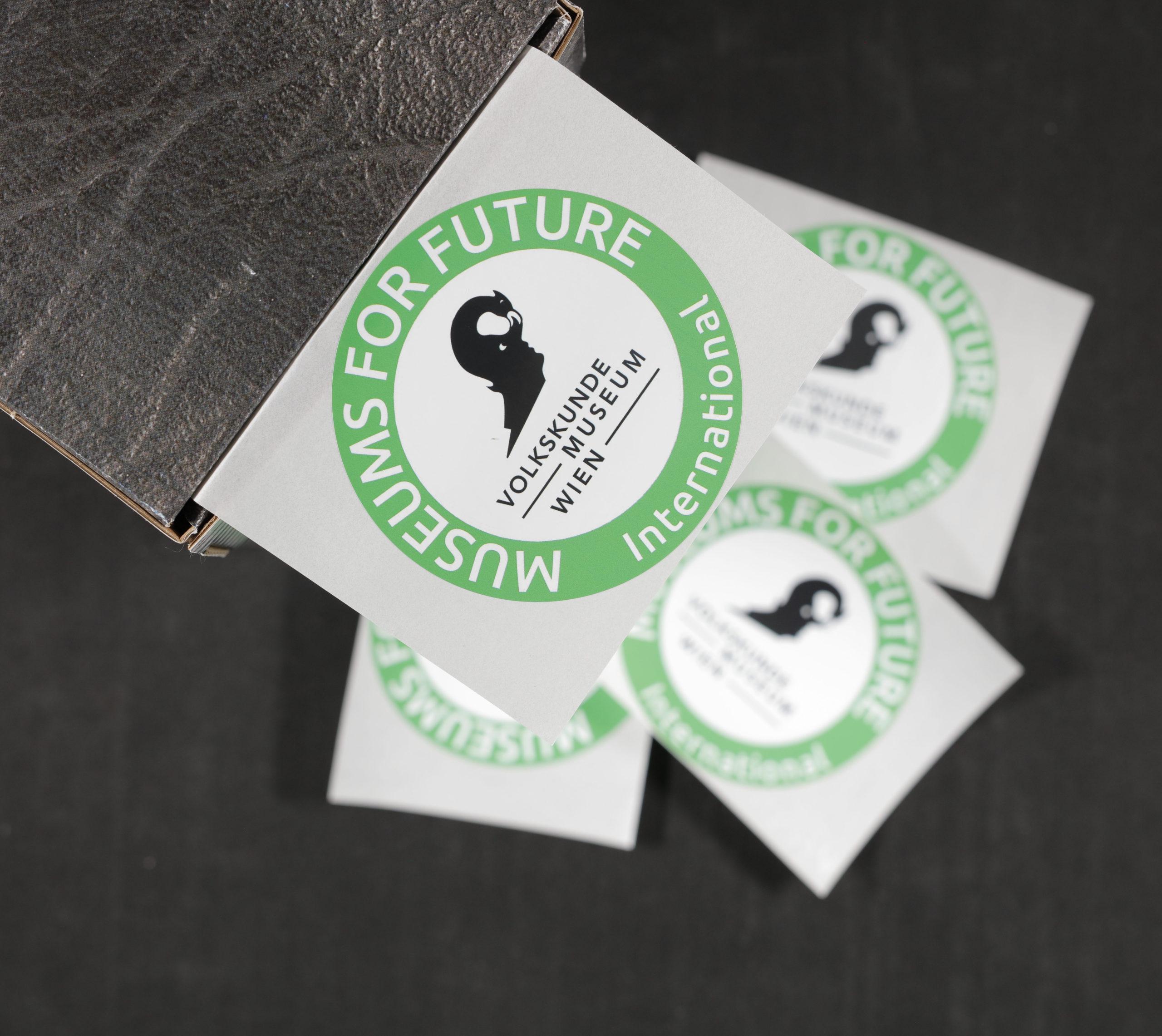 """Foto von Logo-Stickern. Das Logo des Museums ist in der Mitte eingebettet, darum herum verläuft der Schriftzug """"Museums For Future International""""."""