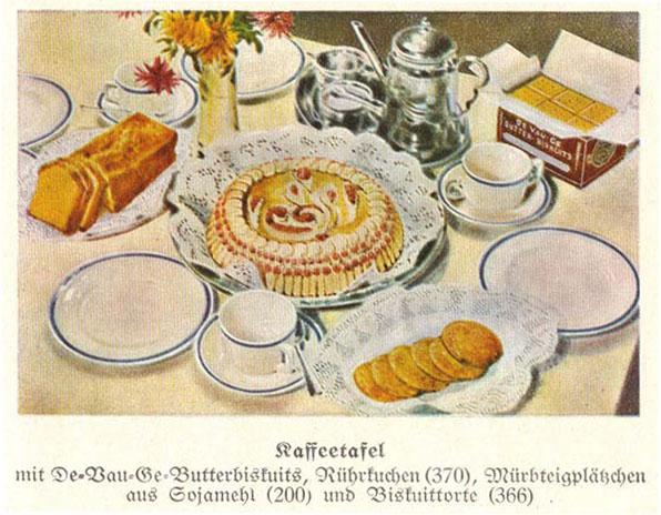 """Die farbige Abbildung aus dem Buch """"Neuzeitliche Küche"""" zeigt eine reichhaltig gedeckte """"Kaffeetafel"""" mit verschiedenem Gebäck. Wie der Untertitelung zu entnehmen, sind etwa die Mürbteigplätzchen aus Sojamehl."""