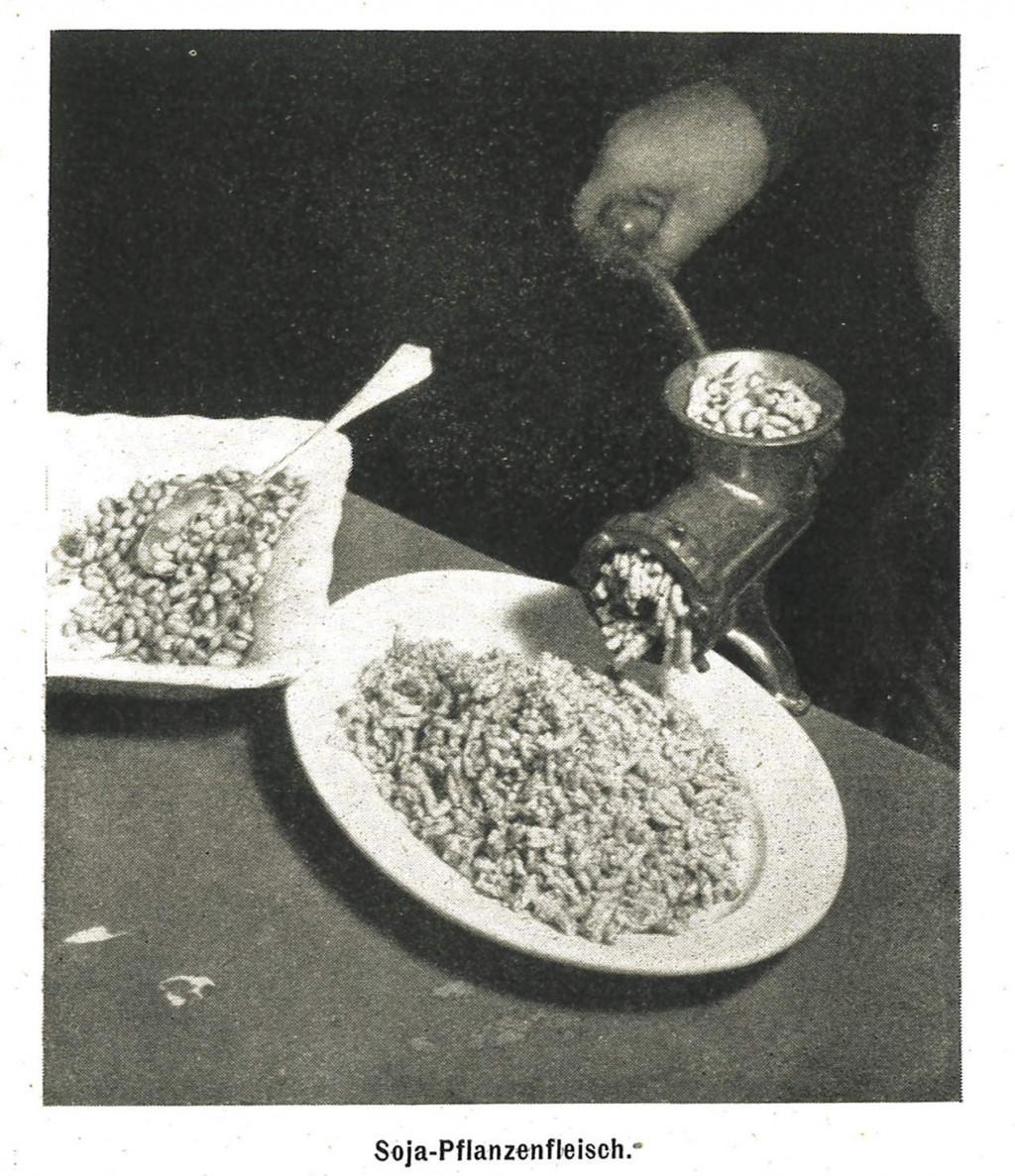 """Die mit """"Soja-Pflanzenfleisch"""" untertitelte Abbildung aus dem Buch """"Wiener Soja-Küche"""" zeigt eine Fotografie, in der Soja mittels einer handbetriebenen Fleischwolfanlage verarbeitet wird."""