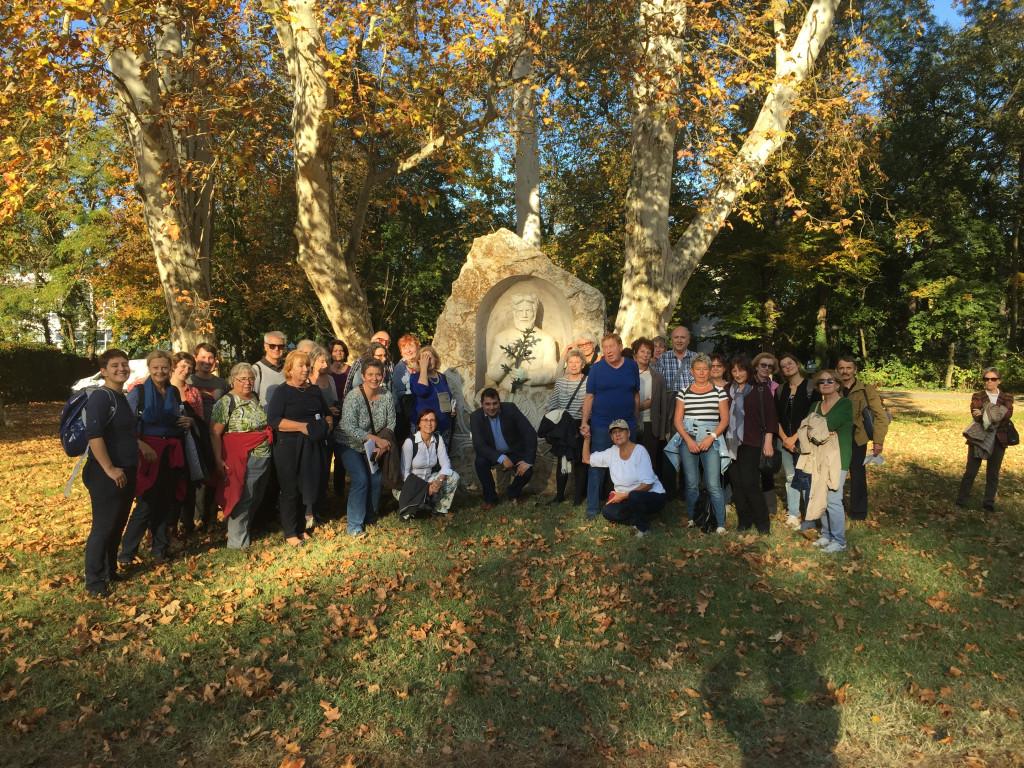 Foto einer Reisegruppe vor einem steinernen Denkmal in einer herbstlichen Parkanlage.
