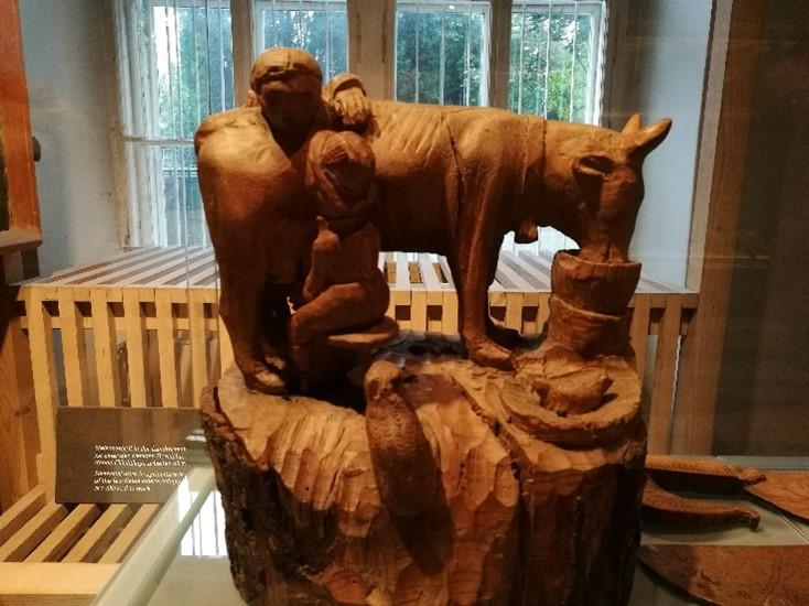 Foto einer hölzernen Skulptur in einem Ausstellungssetting: Melkszene mit einer Kuh, die aus einem Eimer frisst, und zwei Menschen.