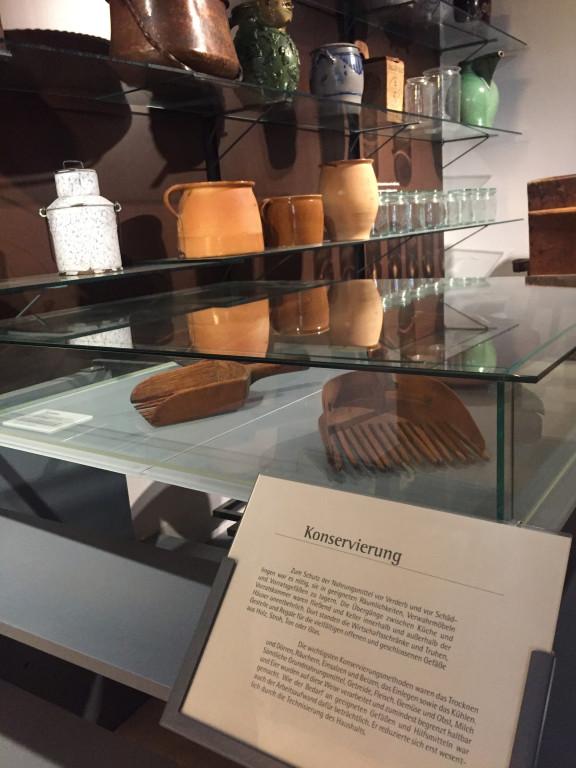 """Das Foto zeigt einen Ausschnitt aus der Dauerausstellung des Volkskundemuseum Wien. Das Beschreibungsschild im Vordergrund ist mit """"Konservierung"""" betitelt, im Hintergrund sind Aufbewahrungsbehältnisse zu sehen."""