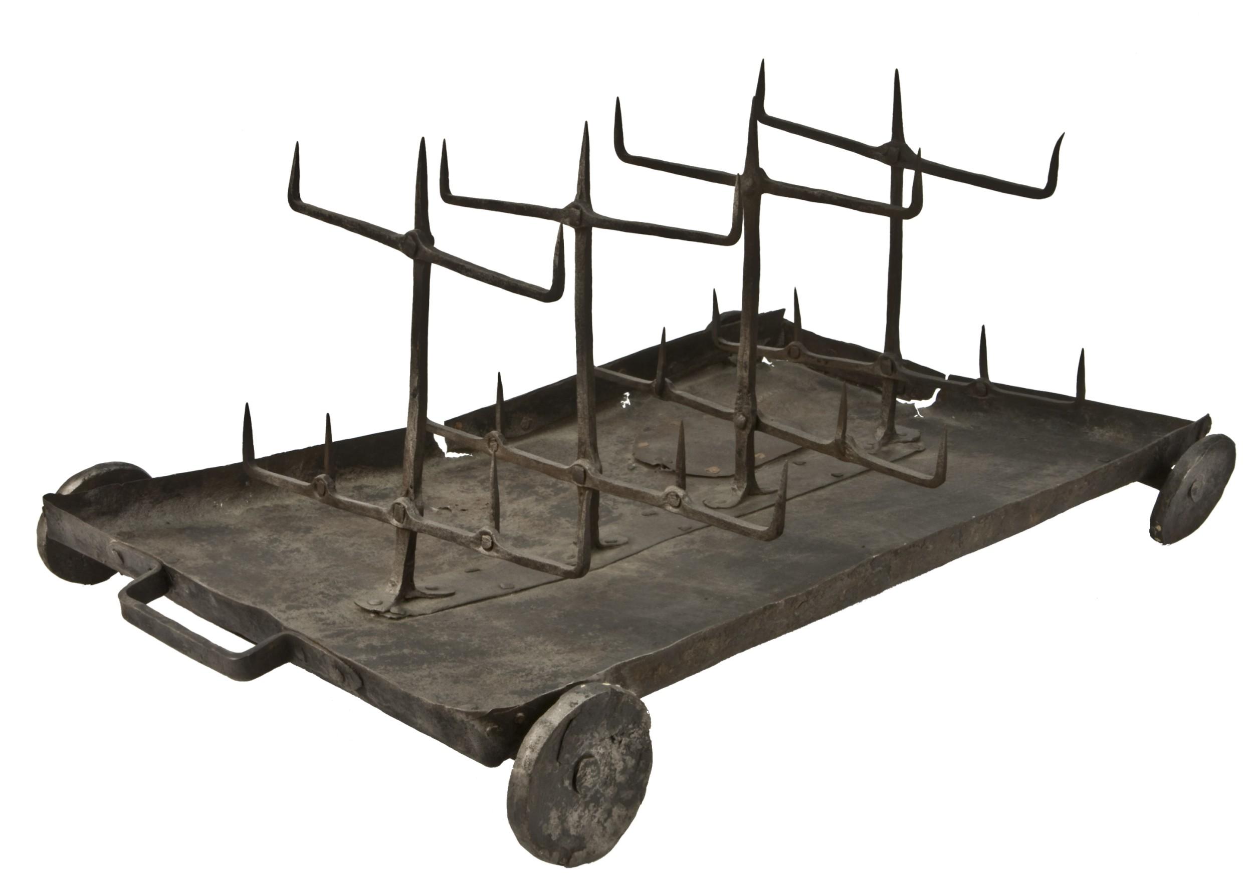 Das Foto zeigt eine Metallplatte auf kleinen Rädern, auf der Spieße montiert sind.