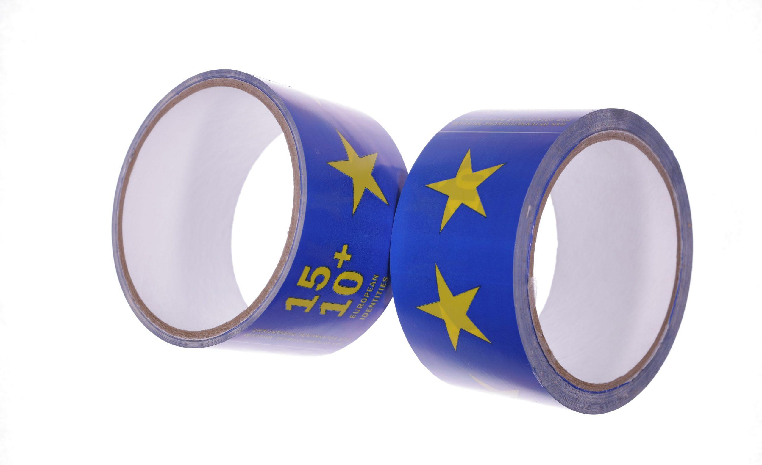 """Das Foto zeigt zwei Klebebandrollen. Sie sind blau, mit aufgedruckten gelben fünfzackigen Sternen und dem immer wieder eingeschobenen Schriftzug """"15+10 Europäische Identitäten""""."""
