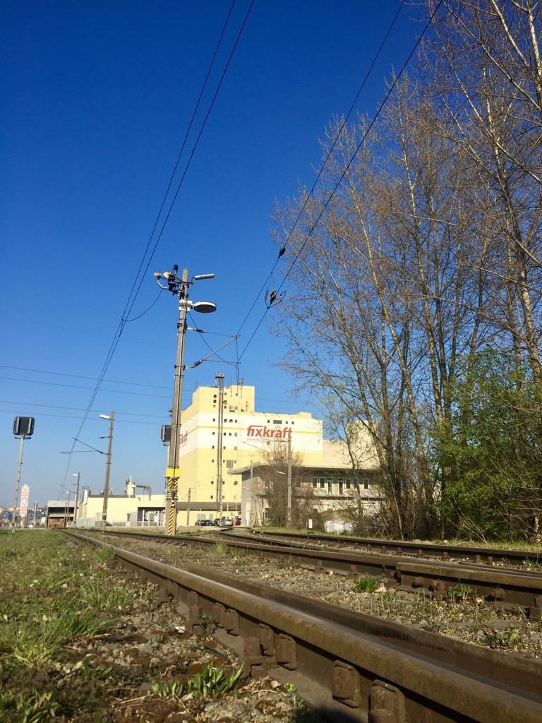 Das Foto zeigt im Vordergrund Zuggleise, im Hintergrund befindet sich eine Industrieanlage des Futtermittelanbieters Fixkraft.