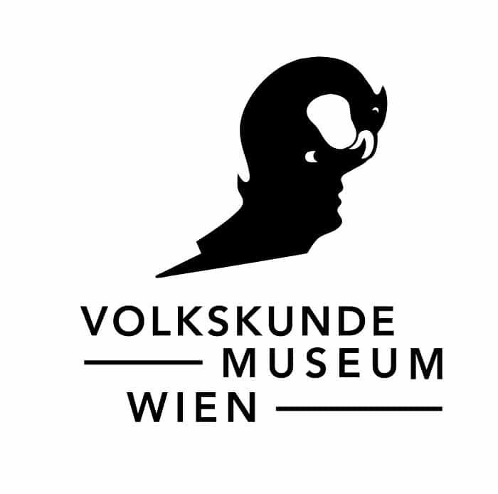 Logo des Volkskundemuseum Wien, das neben dem Namen des Museums die stilisierte Figur des Vogel Selbsterkenntnis beinhaltet: Ein Vogel mit menschlichem Gesicht auf der Brust, der sich selbst bei der Nase packt.