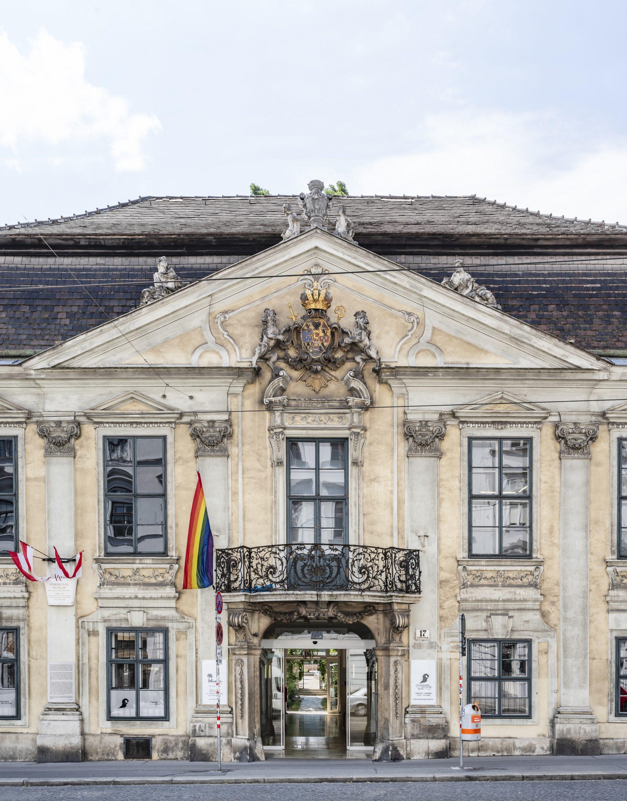Foto vom Haupteingang des Volkskundemuseum Wien mit öffentlichem Durchgang und Regenbogenfahne.