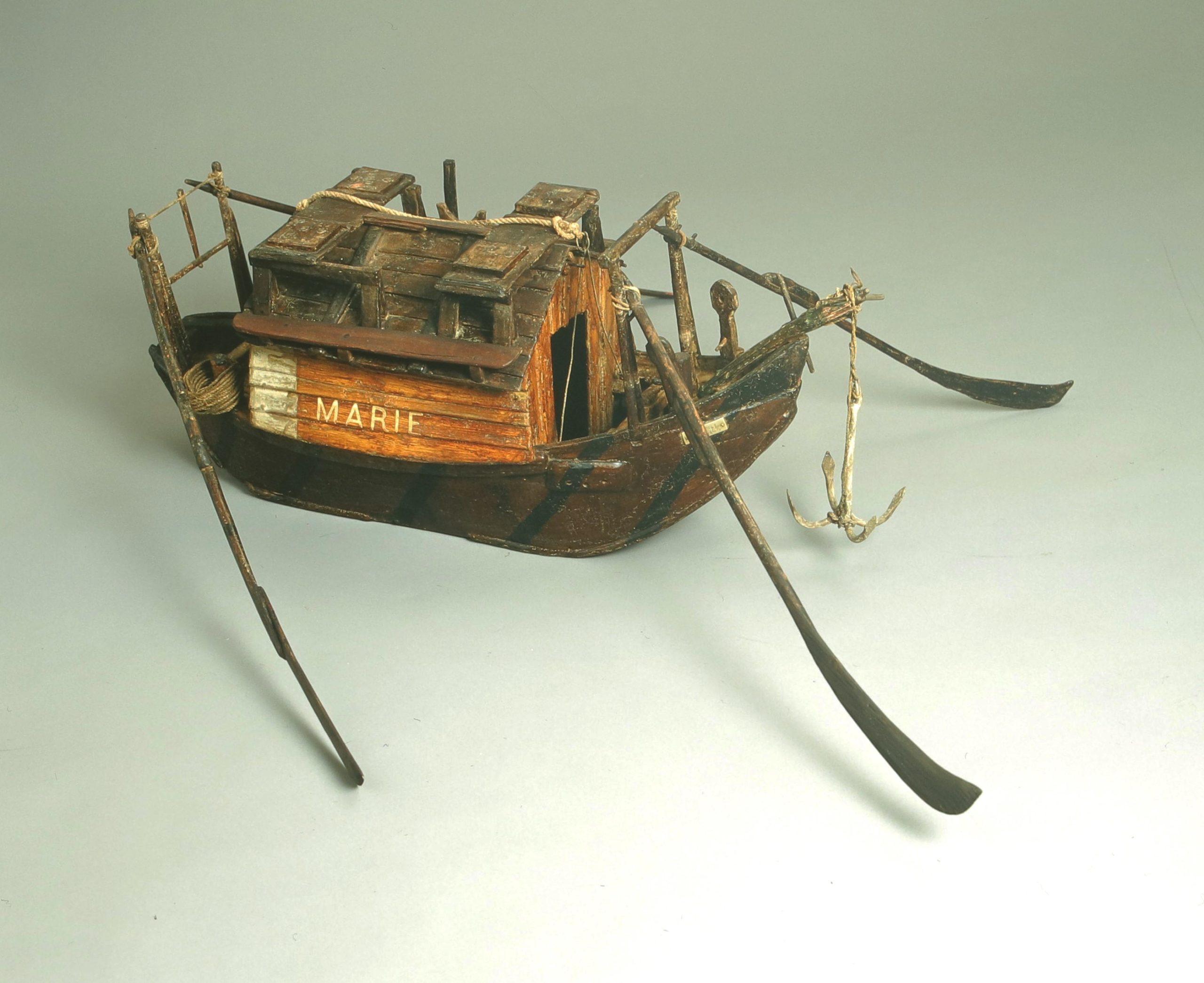 Das Foto zeigt ein hölzernes Modell eines Holzschiffes mit Aufbau und vier Rudern.
